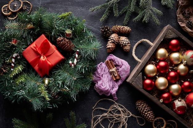 Corona de navidad y adornos para árboles sobre fondo de hormigón negro