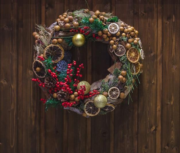 Corona de navidad con bayas de acebo y rodaja de naranja seca colgada en la puerta