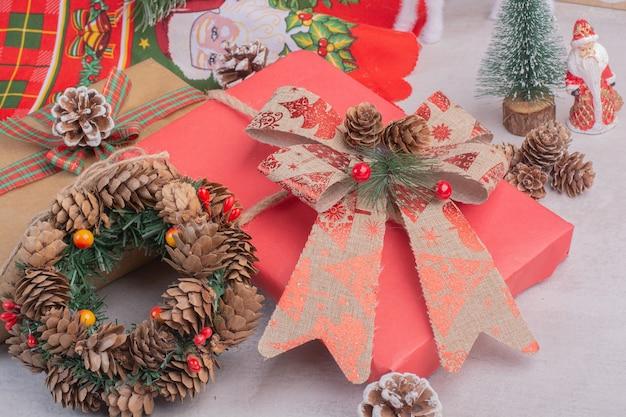 Corona de navidad con cajas de regalo en superficie blanca