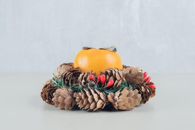 Una corona de navidad con un caqui fresco entero.