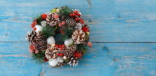Corona de navidad con conos en una tabla de madera