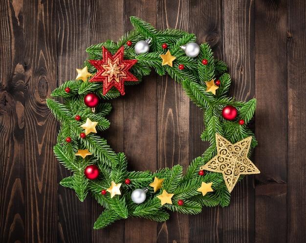 La corona de navidad con decoración de ramas de abeto de abeto se enrolla en un círculo y una estrella de adorno