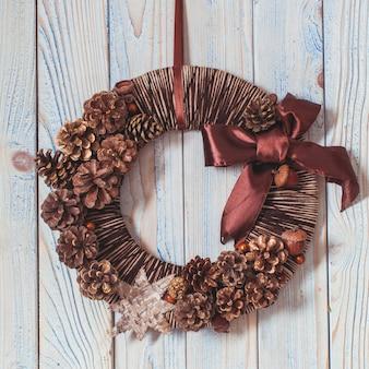 Corona de navidad ecológica natural colgada en la pared azul vintage