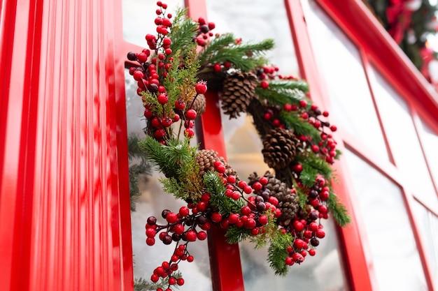 Corona de navidad de frutos rojos, conos y ramas de árboles de navidad en la puerta.