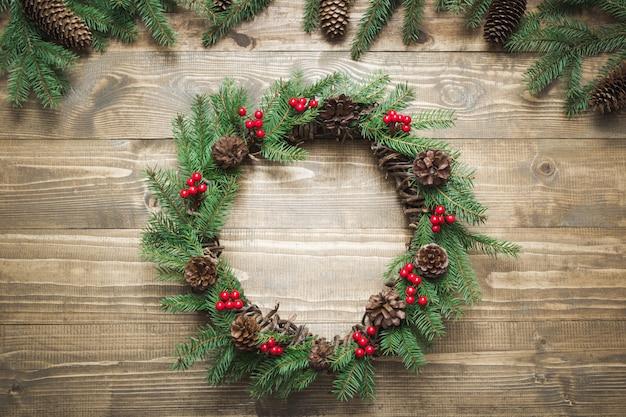Corona de navidad hecha de ramas de abeto con bayas de acebo sobre tabla de madera.