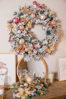 Corona de navidad hecha de ramas de abeto natural colgando de una pared beige.