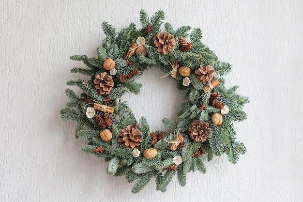Corona de navidad hecha de ramas de abeto natural colgando de una pared blanca.