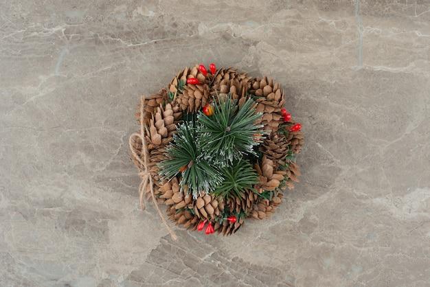 Corona de navidad con perlas rojas y conos sobre mármol.