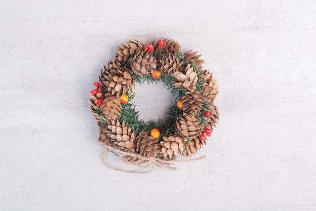 Corona de navidad con perlas rojas sobre mesa blanca.