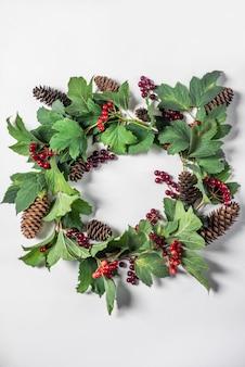 Corona de navidad, rama con frutos rojos, hojas verdes y conos de abeto con espacio para texto sobre fondo blanco.