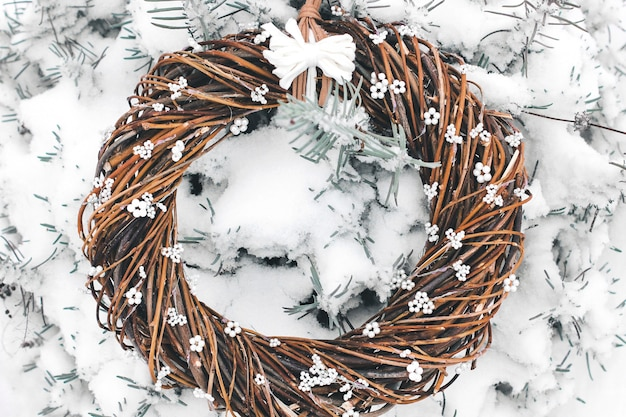 Corona de navidad de ramas. corona hecha a mano en la puerta en la nieve. decoración de invierno