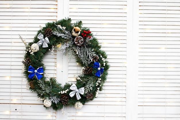 Corona de navidad de ramas de navidad y juguetes decorativos en un blanco
