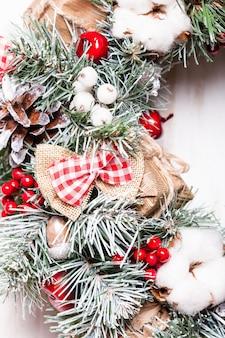 Corona de navidad roja y blanca con lazos y flores de algodón