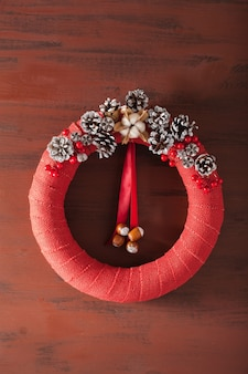Corona de navidad roja sobre fondo de madera