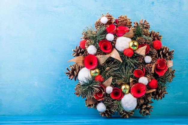Corona de navidad sobre fondo de madera azul en estudio fotográfico