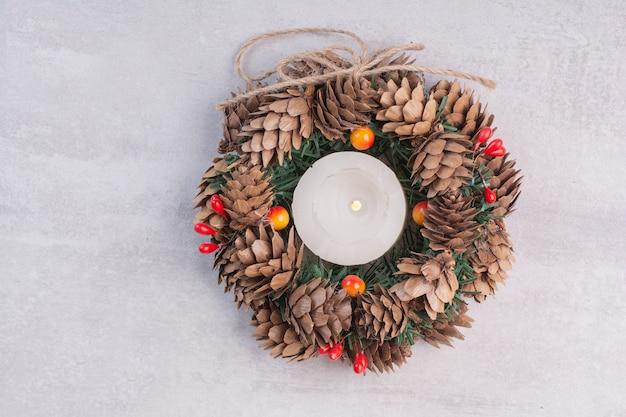Corona de navidad y velas en superficie blanca