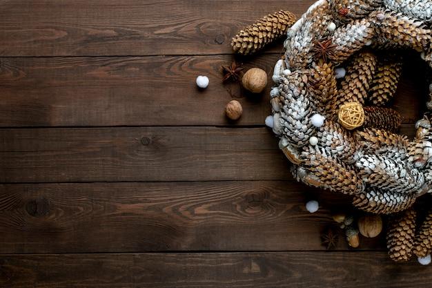 Corona navideña de conos en una mesa de madera