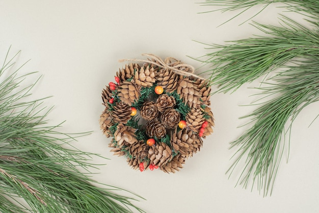Corona navideña decorada con piñas y bayas de acebo