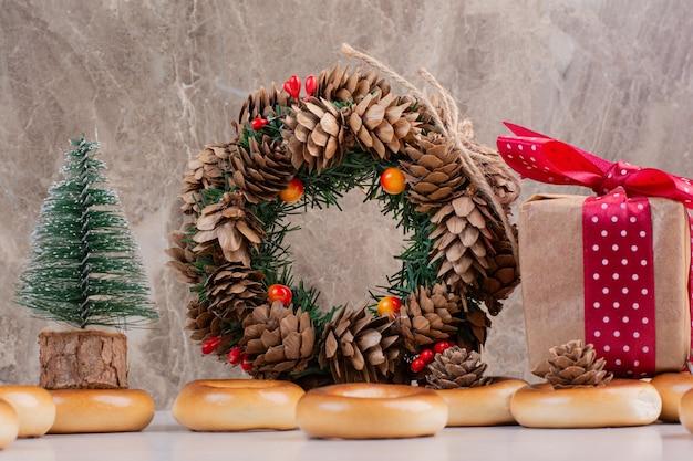 Corona navideña de piñas con galletas y pequeña caja de regalo. foto de alta calidad