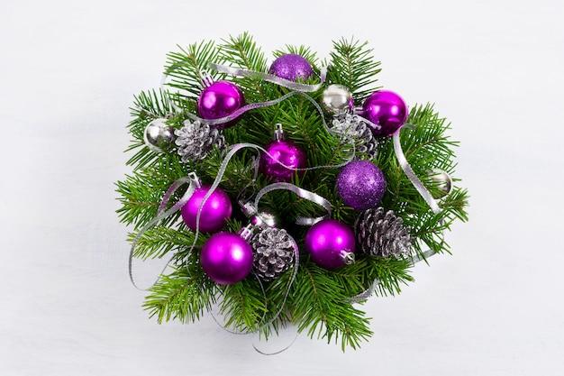 Corona navideña con piñas de plata y adornos de color púrpura.