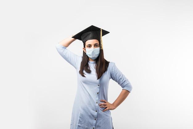 Corona pandemia y confusión por los exámenes universitarios en india - bonita estudiante india con expresiones confusas con mascarilla médica y sombrero de graduación