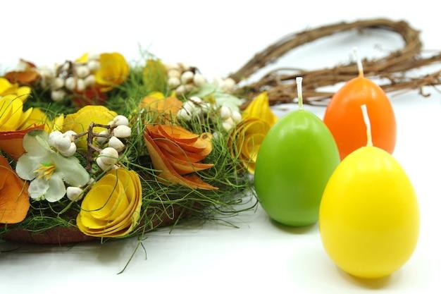 Corona de pascua decorada con flores en la superficie blanca coloridas velas de pascua concepto de pascua