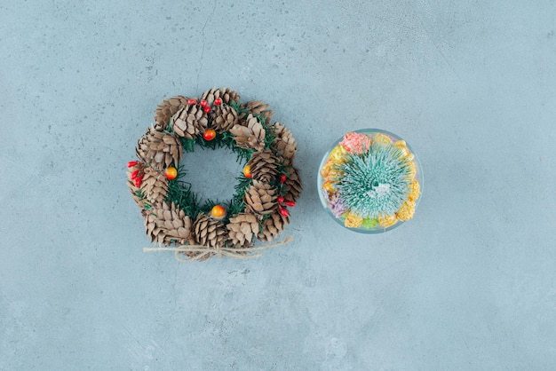 Corona de pino y porta caramelos con noguls y una figura de árbol en mármol.