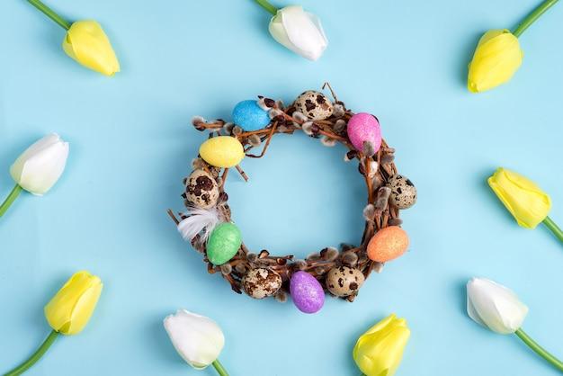 Corona de sauce de pascua y coloridos huevos de pascua con tulipanes