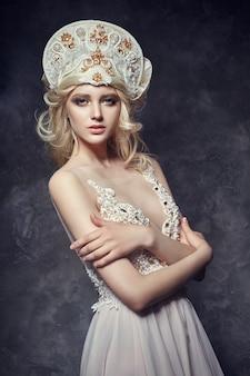 Corona de tiara en la cabeza de niña rubia. vestido de hada mujer