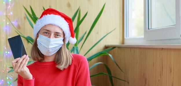 Coronavirus y celebración de año nuevo en autoaislamiento navidad en línea felicitaciones a una mujer con sombreros rojos de santa