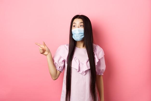 Coronavirus, concepto de cuarentena y estilo de vida. emocionada muchacha adolescente asiática en mascarilla apuntando, mirando a la izquierda en el logotipo con cara de asombro, mirando la promoción, fondo blanco.