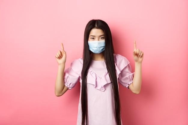 Coronavirus, concepto de cuarentena y estilo de vida. hermosa mujer asiática en máscara médica estéril apuntando con el dedo hacia arriba, sonriendo con ojos y mirada confiada, de pie contra el fondo rosa.