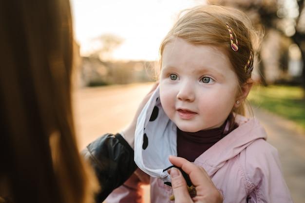 Coronavirus el concepto final. no más covid-19. niña, madre usa máscaras a pie en la calle. mamá se quita la máscara de niño feliz. familia con niños al aire libre. celebrando el éxito la pandemia ha terminado, ha terminado.