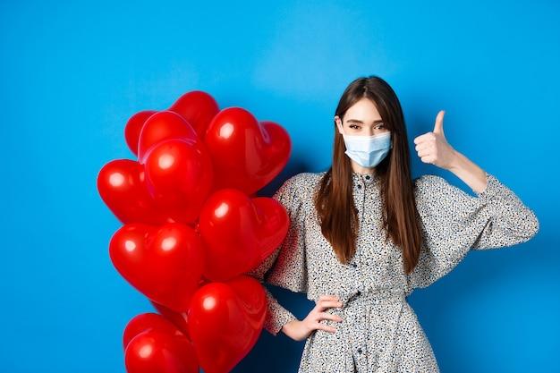 Coronavirus y concepto de pandemia. hermosa mujer en máscara médica y vestido de pie cerca de globos de san valentín y mostrando el pulgar hacia arriba, de pie sobre fondo azul.