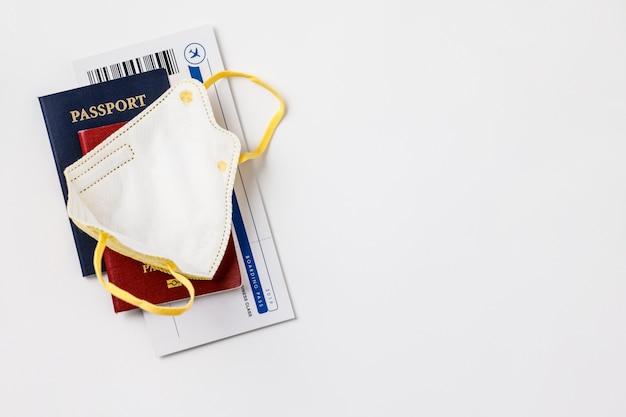 Coronavirus y concepto de viaje. pasaportes, boletos de avión y mascarilla médica.