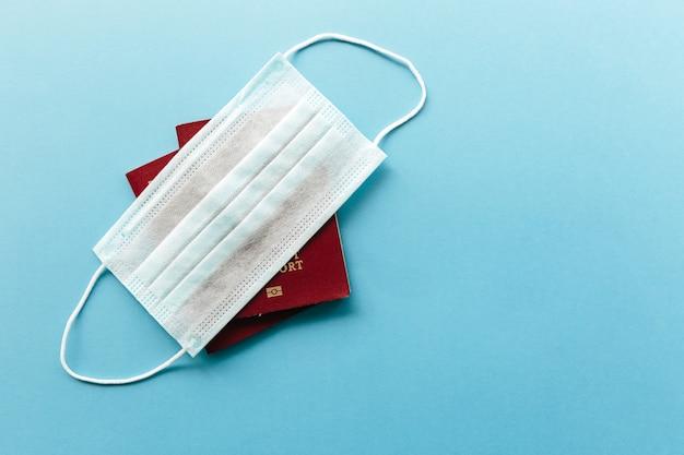 Coronavirus y concepto de viaje. pasaportes y mascarilla médica plana