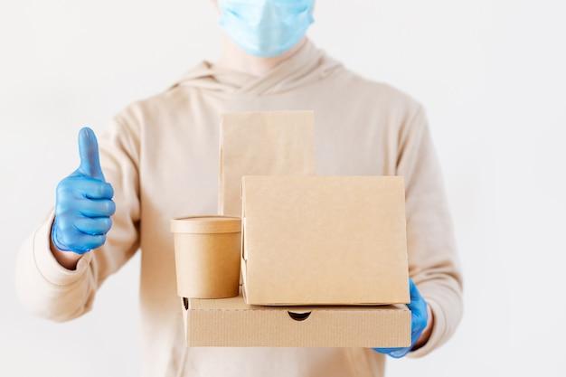 Coronavirus epidémico. café, paquete de comida rápida. entrega de comida sin contacto. un mensajero con guantes y una máscara sostiene un embalaje ecológico. quédate en casa, mantente a salvo