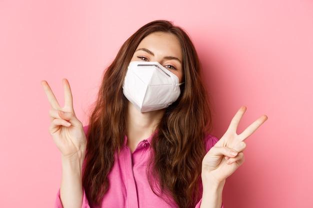Coronavirus, medidas preventivas y concepto de salud. cerrar retrato mujer positiva en respirador médico, posando y mirando feliz con paz v-signos, pared rosa.