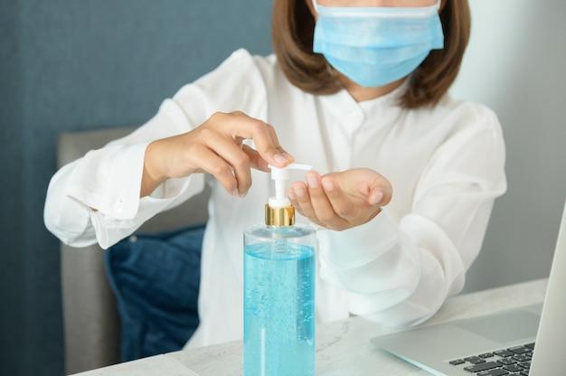Coronavirus. mujer de negocios trabajando desde casa con máscara protectora. mujer de negocios en cuarentena para coronavirus con máscara protectora. trabajando desde casa. limpiándose las manos con gel desinfectante.