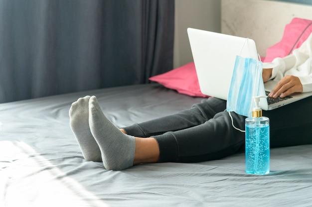 Coronavirus. mujer de negocios trabajando desde casa, mujer de negocios en cuarentena para coronavirus, gel desinfectante y máscara protectora en la cama, enfoque selectivo
