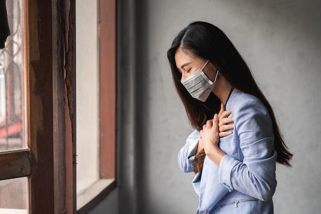 El coronavirus pandémico covid-19, mujer asiática con máscara, tiene síntomas de tos y fiebre