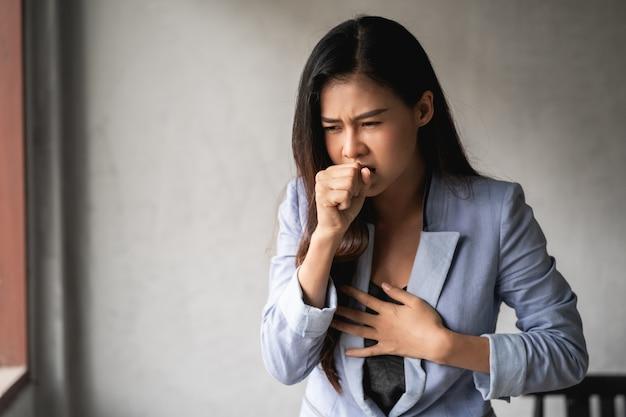 El coronavirus pandémico covid-19, mujer asiática tiene un resfriado y síntomas de tos, fiebre, dolor de cabeza y dolores
