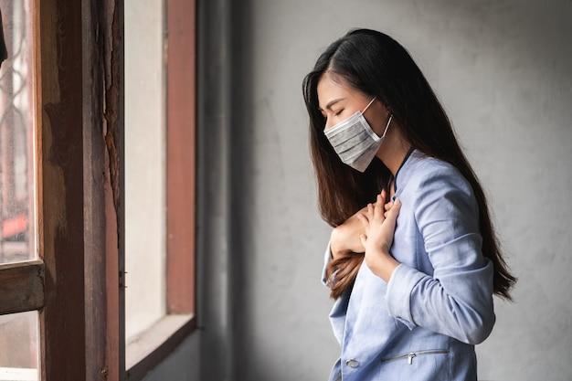 Coronavirus pandémico covid-19, mujer asiática tiene un resfriado y síntomas de tos, fiebre, dolor de cabeza y dolores