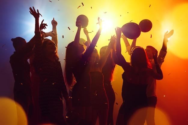 Corporativo. una multitud de personas en silueta levanta sus manos en la pista de baile sobre fondo de luz de neón. vida nocturna, club, música, baile, movimiento, juventud. colores amarillo-azul y niñas y niños en movimiento.