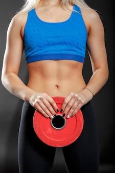 El corpus de una mujer con las manos sosteniendo el disco de pesas con barra