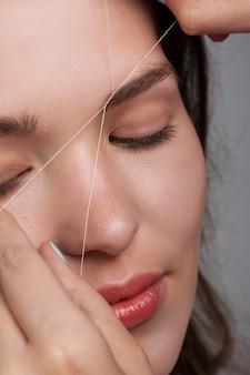 Corrección de cejas con hilo blanco