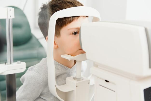Corrección de la visión en un niño. cara de primer plano del niño paciente. equipo súper moderno en una clínica moderna para examen ocular