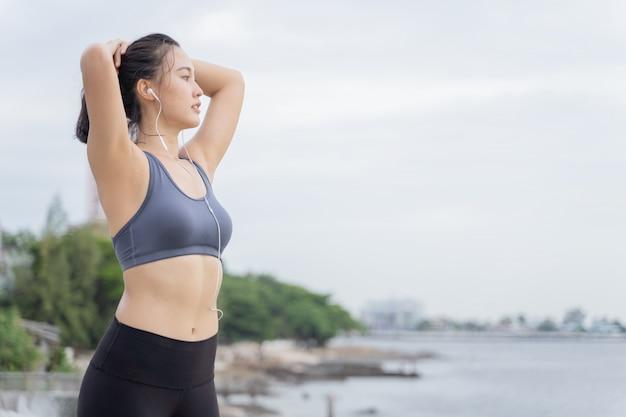 Corredor asiático joven de la mujer que descansa después de entrenamiento que corre en playa de la playa.