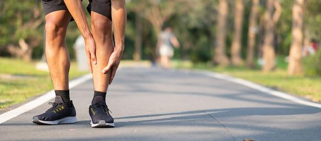 Corredor asiático que tiene dolor de pantorrilla y problema después de correr y hacer ejercicio afuera