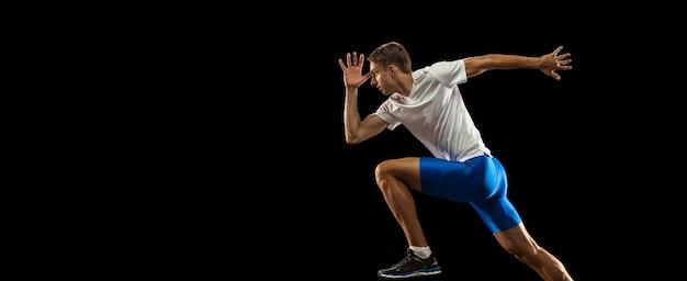 Un corredor de atleta masculino profesional caucásico entrenamiento aislado en la oscuridad
